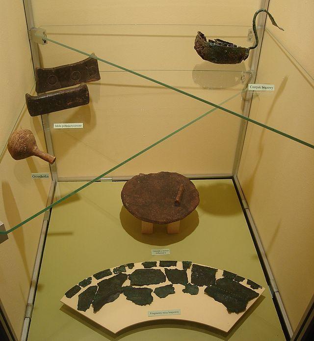 Grzechotka, czerpak brązowy, talerzyk, idole, fragmenty misy brązowej
