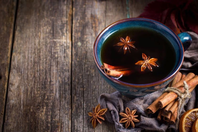 Cup of hot spicy tea with anise and cinnamon, selective focus, copy space